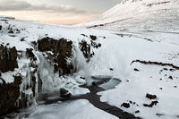 Closeup of waterfall in front of Kirkjufell mountain at sunset, Iceland
