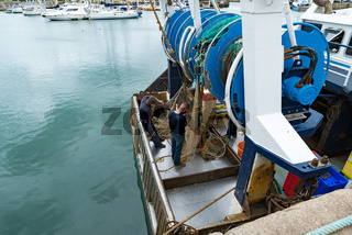fishermen repair fishing nets on their fishing boat in the harbor