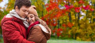 happy teenage couple hugging in autumn park