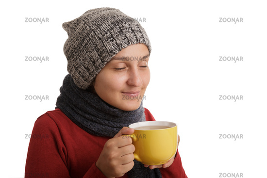 A young woman drinks a cup of hot tea in the winter time isolated on white background.