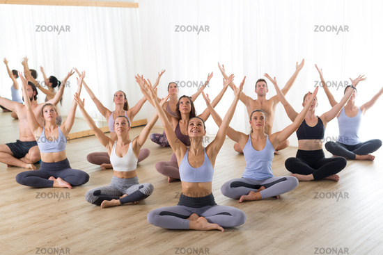 Group of young sporty attractive people in yoga studio, practicing yoga lesson with instructor, sitting on floor in Padmasana, lotus meditative yoga pose. Healthy active lifestyle, working out in gym