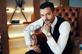 Handsome young man sitting and posing in armchair in modern luxury interior