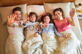 Fröhliche Eltern und zwei Kinder winken