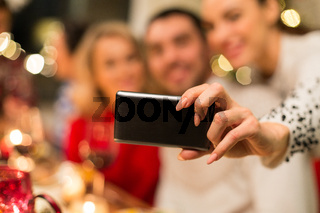 close up of friends taking selfie on christmas