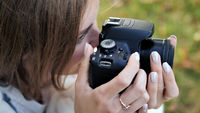 The girl takes pictures of nature in the park in the summer. Hands with a photo camera close-up.