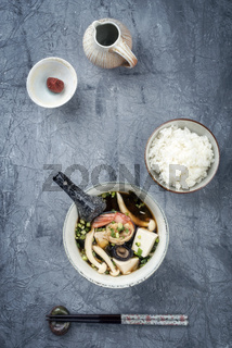 Traditional Japanese miso soup with king prawns and rice as top view in a bowl with copy space