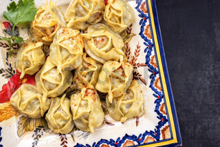 Traditional Kazakh manti steamed with mincemeat as top view on a plate