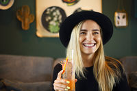 Attractive cute caucasian girl in black tshirt and black hat drinkig cold citrus juice or lemonade