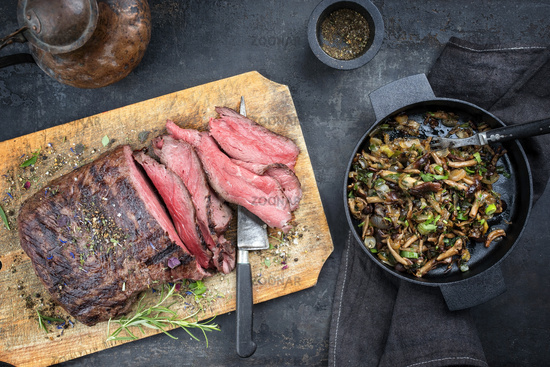Traditional barbecue dry aged sliced roast beef steak with fried pioppino as top view on an old cutting board