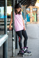 Young brunette woman on rollerskate smiling