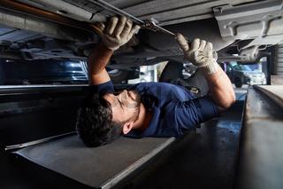 KFZ Mechaniker kontrolliert Auto Unterbodenschutz