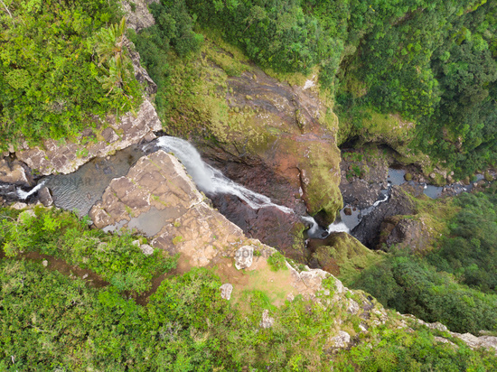 Aerial top view of travel couple waving to drone, standing on the edge of 500 feet waterfall in the tropical island jungle of Black river gorges national park on Mauritius island