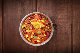 Chili con carne, overhead shot on a dark rustic wooden background with a nacho chip