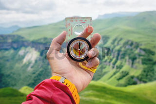 Male hand is holding a magnetic compass on the background of hills and the sky with clouds. The concept of traveling and finding your life path
