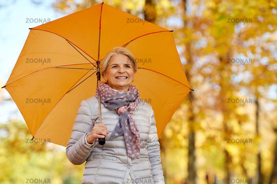 happy senior woman with umbrella at autumn park