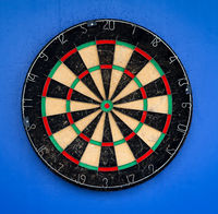 A dartboard in front of a blue background