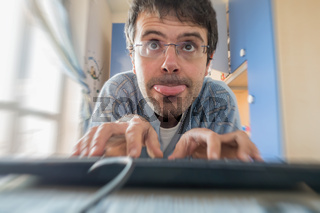 Young man in pajamas addicted to computer and smartphone in the bedroom.