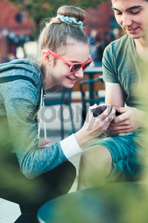 Teenage girl and boy,  having fun with smartphones, sitting in center of town