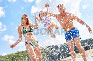 Eltern plantschen und spritzen mit Wasser