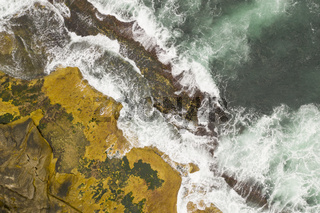 Aerial shot ofr rock ledge and crashing waves