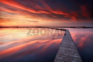 long pier on big lake at sunset