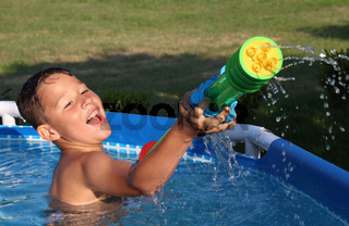 Kleiner Junge im Pool mit Wasserspritze