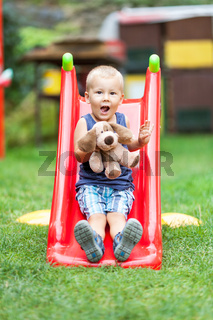 Adorable child playing outdoors on the slide
