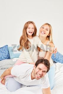 Eltern lachen und albern mit ihrer Tochter herum