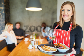 Freundliche junge Kellnerin mit Vorspeisen