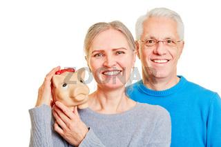 Zwei Senioren halten Sparschwein als Geldanlage