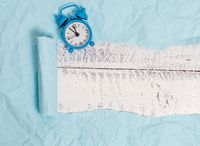 Ripped cardboard with a mini alarm clock placed above a wooden classic table. Thick torn paper on a textured wood backdrop. Artistic way of arranging flat lays photography