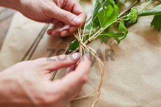 Hände von Florist beim Blumen binden mit Bast