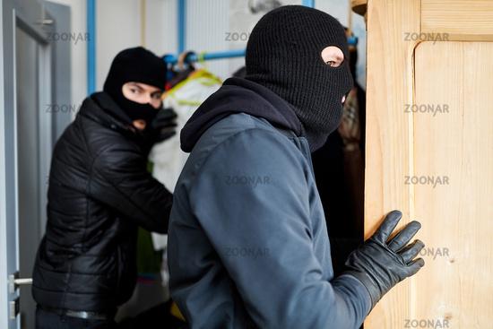 Zwei Einbrecher suchen Wertsachen in Haus