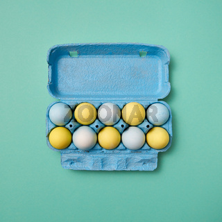Blue cardboard box with colorful yellow and blue painted Easter eggs presented on a green background with copy space. Flat lay