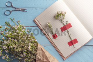 White flowers and an open agenda on a blue table