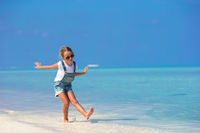 Cute happy little girl have fun on beach vacation