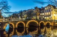 Amstedam, capital of Netherlands. Beautiful city of Amsterdam illuminated at dusk. Bicycles along the street and on the bridge over the canal
