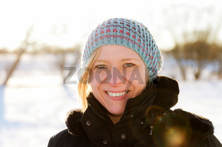 Blonde woman walking outdoors in a snowy winter landscape scene. Christmas time and winter wear concept.