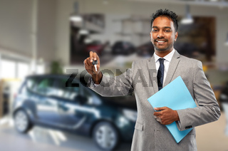 happy indian car dealer with car key at showroom