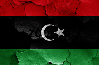 flag of Libya painted on cracked wall