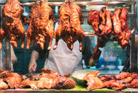 Roast crispy Chinese duck and pork hanging from market stall window of a street food vendor