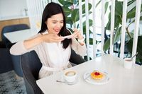 woman photographing coffee by smartphone at cafe
