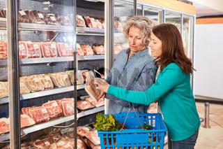 Frau scannt Barcode mit Smartphone im Supermarkt