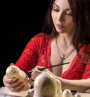 Woman painting nested doll - russian matryoshka