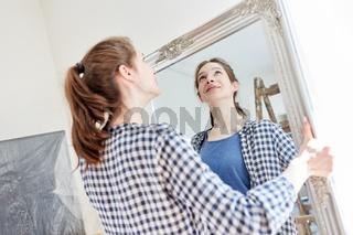 Frau beim Umzug hängt einen Spiegel auf