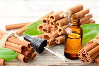 cinnamon oil in the glass bottle, on the wooden board