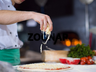 chef sprinkling cheese over fresh pizza dough