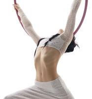 Pretty brunette perfoming aerial exercise on hoop