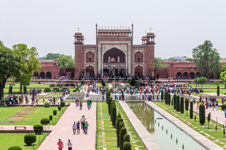 Great Entrance Gate with walkway, garden square, reflecting pool and visitors taken from Taj Mahal. Agra, Uttar Pradesh, India