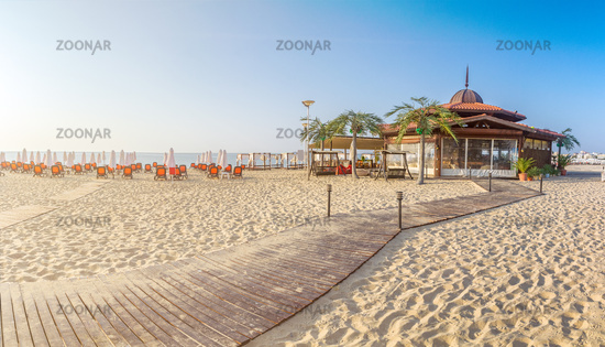 A bar at the beach with chairs and umbrellas on a beautiful beach at sunrise in Sunny Beach on the Black Sea coast of Bulgaria. Panoramic view
